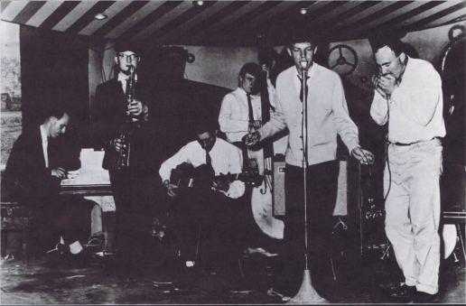 Um Mick Jagger adolescente canta no Blues Incorporated, com Jack Bruce ao fundo no baixo acústico.